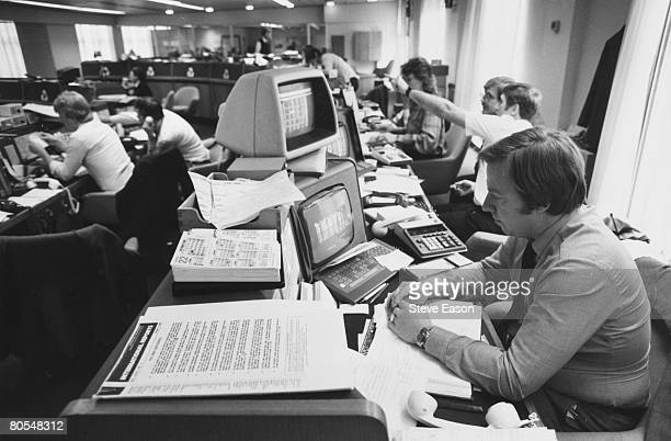 Staff at work at computer screens in a modern office in the City of London circa 1990