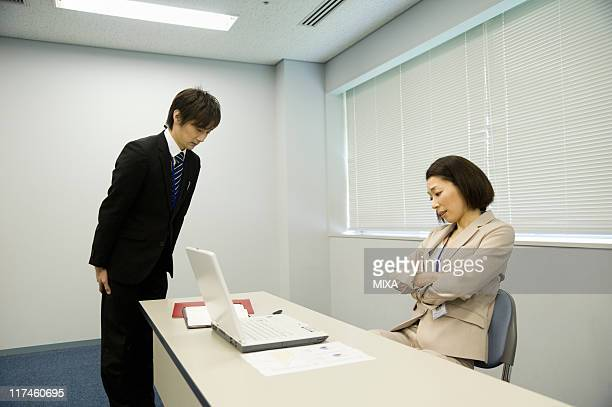 Staff bowing to boss at office