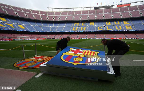Staff carry a giant Barcelona crest across the pitch before the UEFA Champions League match between FC Barcelona and Arsenal at Camp Nou on March 16...