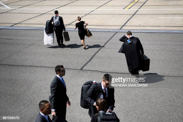 Staff carry luggage from Air Force One at London Stansted Airport north of London on July 12 2018 after the arrival of US President Donald Trump and...