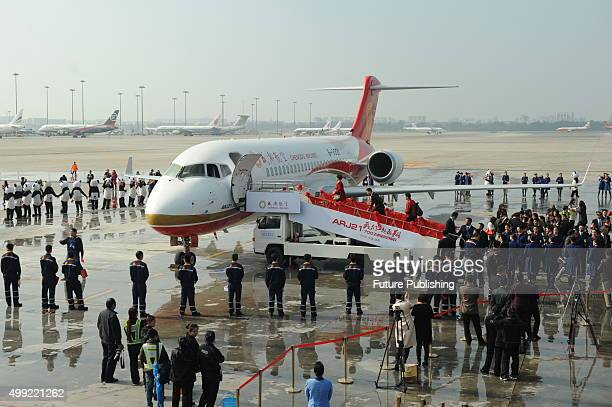 Staff celebrate the arrival of the ARJ21 jet at the airport on November 29 2015 in Chengdu China It is the first ARJ a regional jet made by...