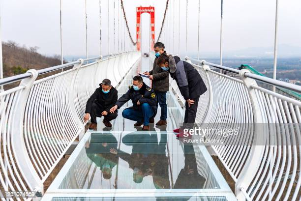Staff check a glass-bottomed trestle at a rural scenic spot in Hefei, Anhui province, China, Feb 10, 2021.Staff check a glass-bottomed trestle at a...