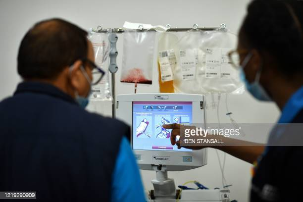 Staff check a monitor as a donor gives blood plasma at a newly opened plasma donor centre in Twickenham, southwest London on June 11, 2020. - It is...