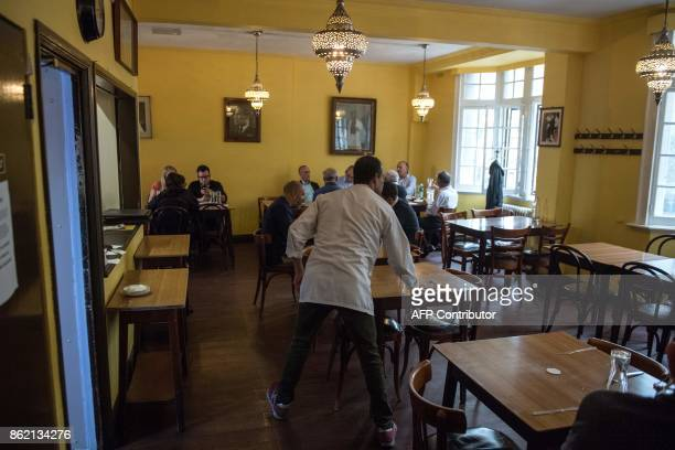 Staff clean tables as people eat lunch inside the India Club restaurant in London on October 16 2017 Plans to renovate a historic and beloved Indian...