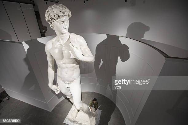 """Staff cleans the duplicate of Michelangelo's David for the exhibition """"The Divine Michelangelo"""" at Shanghai Modern Art Museum on December 25, 2016 in..."""