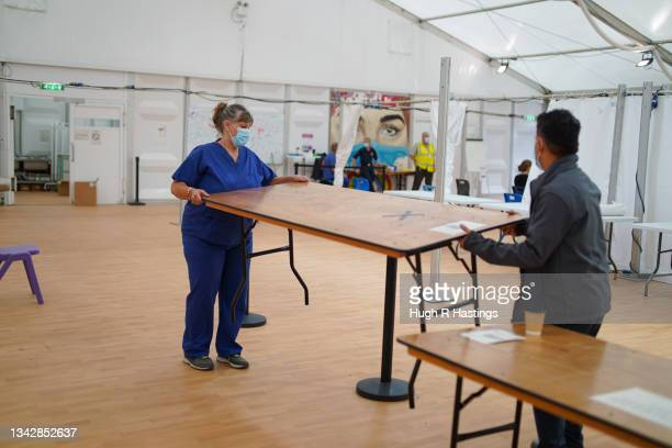 Staff clear away their workstations at the Stithians Showground temporary NHS vaccination after it closed on September 26, 2021 in Stithians, near...