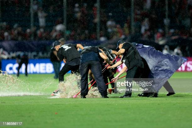 CONMBEBOL staff clear the water from pitch as the match is delayed due to the heavy rain during the final of Copa CONMEBOL Sudamericana 2019 between...