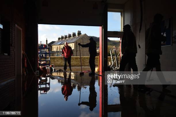 TOPSHOT Staff clear up at the fire station in Mytholmroyd northern England on February 10 2020 after flooding brought by Storm Ciara Storm Ciara...
