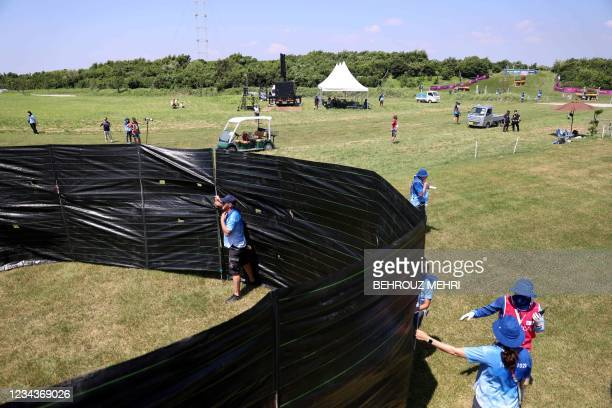 Staff cover around the horse Jet Set of Switzerland's Robin Godel after an injury in the equestrian's eventing team and individual cross country...