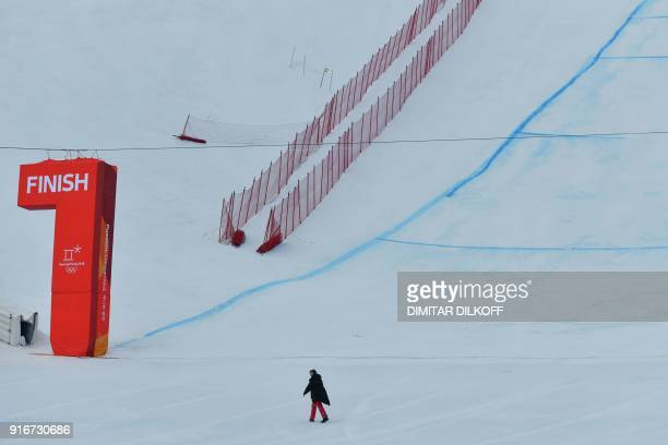 A staff crosses the finish line at the arrival area of the Men's Downhill race at the Jeongseon Alpine Center during the Pyeongchang 2018 Winter...