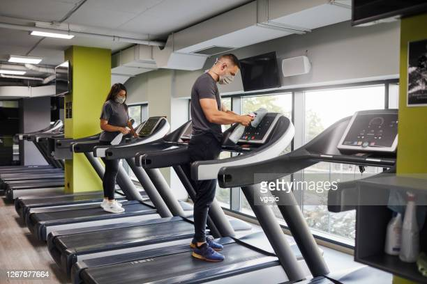staff disinfecting sports equipment in the gym - cleaning agent stock pictures, royalty-free photos & images