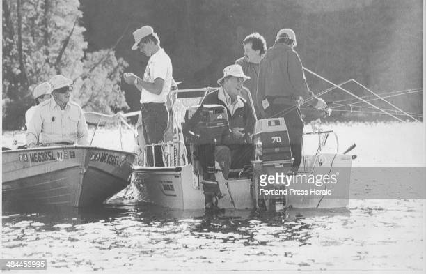 Sir Edmund Hillary wearing white hat and seated in the boat at right fishes at the King and Bartlett Camp in Eustis in July 1993 with business...