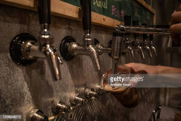 A staff fills a cup of beer for a customer ahead of Hong Kong government's order of a twoweek closure of bars and pubs on April 3 2020 in Hong Kong...
