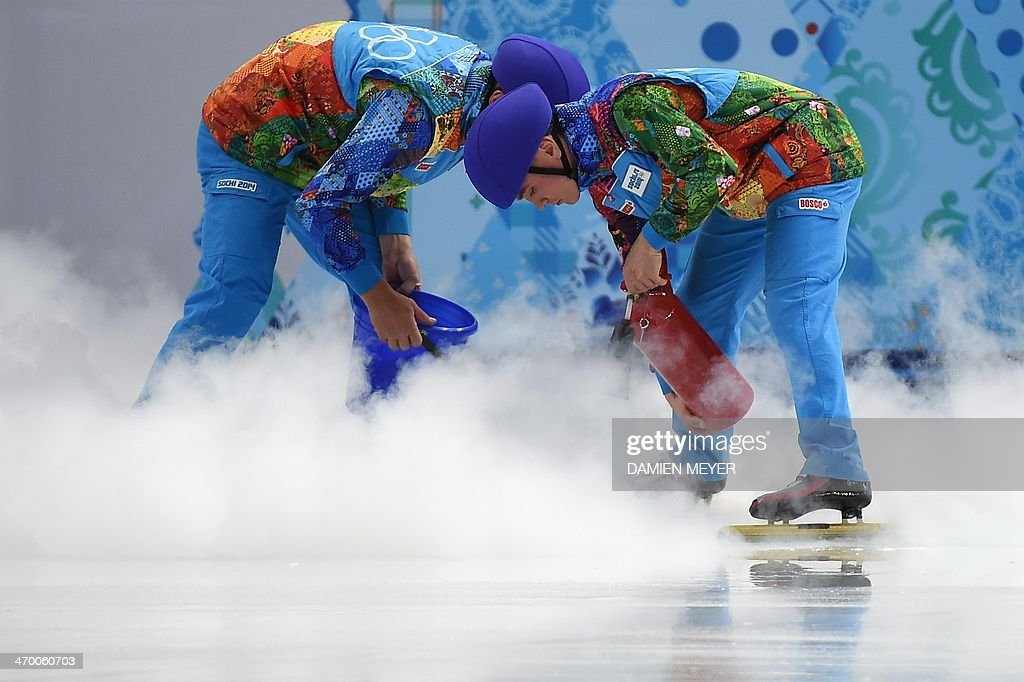 Staff fix the ice during the Men's Short Track 500 m Heat 8 at the Iceberg Skating Palace during the Sochi Winter Olympics on February 18, 2014.