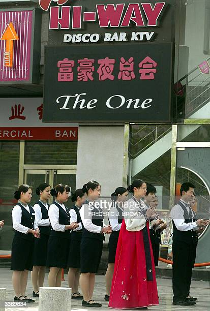 Staff from a Korean restaurant gather for morning exercise and a work update session 15 April 2004 in Beijing China's economy grew by 97 percent in...