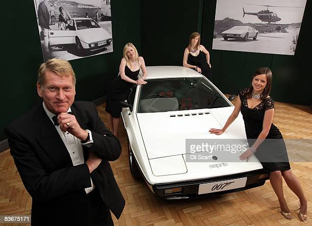 Staff from Bonhams auctioneers dressed as characters from a James Bond film pose with the white 1976 Lotus Esprit car from the 1977 film ' The Spy...
