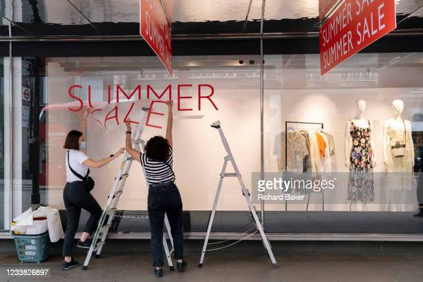 Staff from High Street retailer John Lewis attach sticky transfers for the upcoming John Lewis Summer Sale on Oxford Street, on 5th July 2021, in...