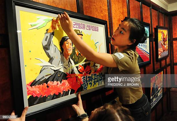 Staff from Koryo Studio in Beijing put up framed North Korean propaganda posters ahead of the opening of an exhibition of propaganda and antiUS...