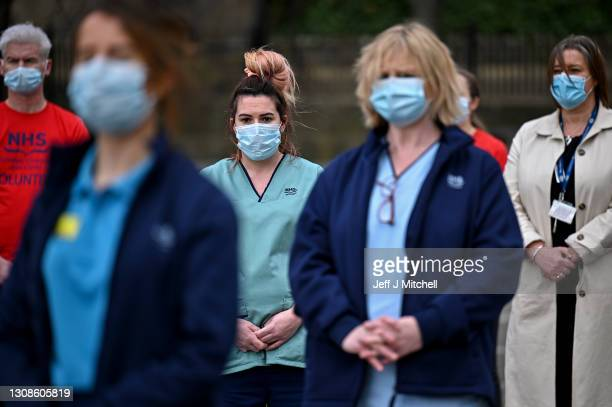 Staff from the Glasgow Royal Infirmary gather outside the hospital for a minute's silence on March 23, 2021 in Glasgow, Scotland. Marie Curie Cancer...