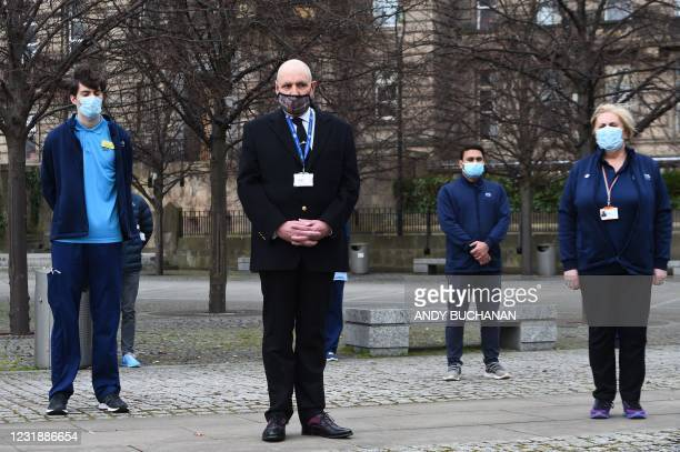 Staff from the Glasgow Royal Infirmary take part in a minutes silence on the first anniversary of the first national Covid-19 lockdown in Glasgow on...