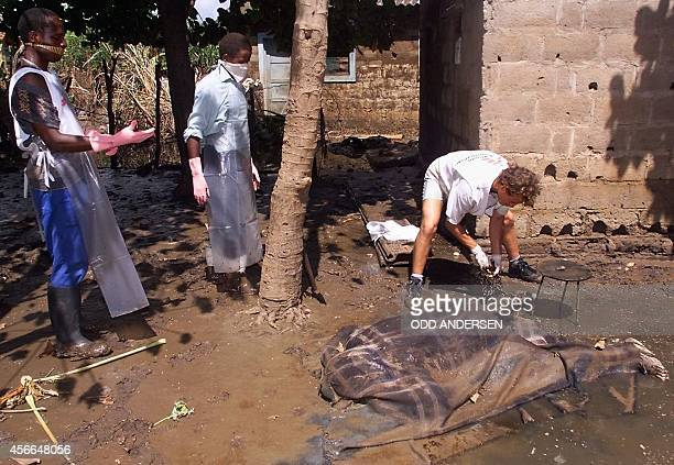 Staff from the international organization Medecins Sans Frontieres cut 05 March 2000 the chain attached to the leg of the decomposed body of Sarafino...