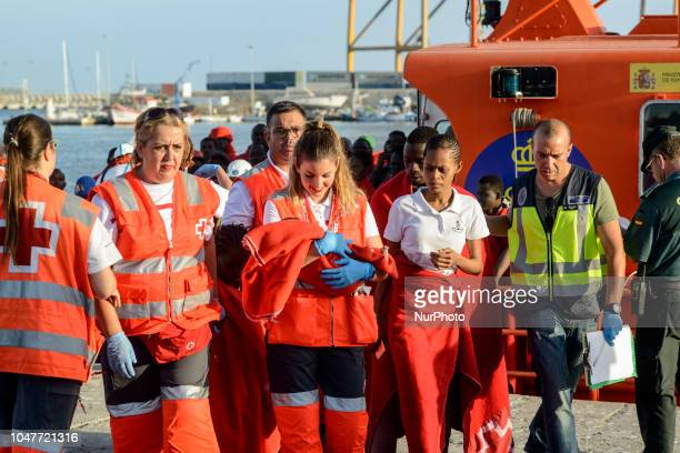 A staff from the Red cross carries a young child to the tent on October 6 Malaga