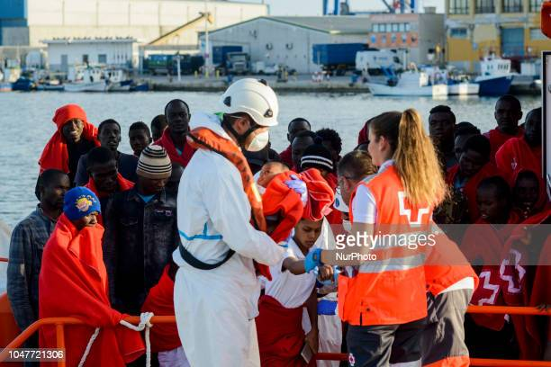 A staff from the Spanish vessel carries a young child to the Red cross tent on October 6 Malaga