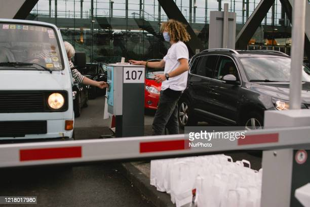 A staff gives instructions to the driver during the opening of drive in Gallery's show Nachtbroetchen 20 at Cologne airport parking lot amid the...