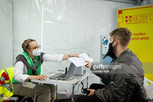 Staff hand over documents and a voucher for a doner kebab to a man after he received a dose of the Moderna vaccine in a temporary vaccination center,...