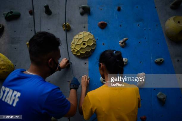 Staff helps by giving directions and guiding him to holds on the climbing route visually impaired people in Astrek Climbing wall at Thamel,...