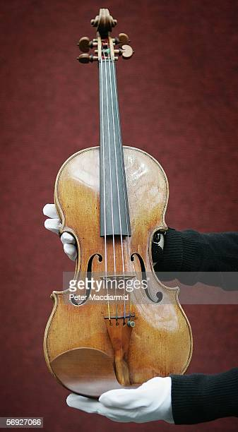 Staff hold a violin made by Antonio Stradivari at Christie's auctioneers on February 24 2006 in London Christie's will put the violin made in 1707 up...