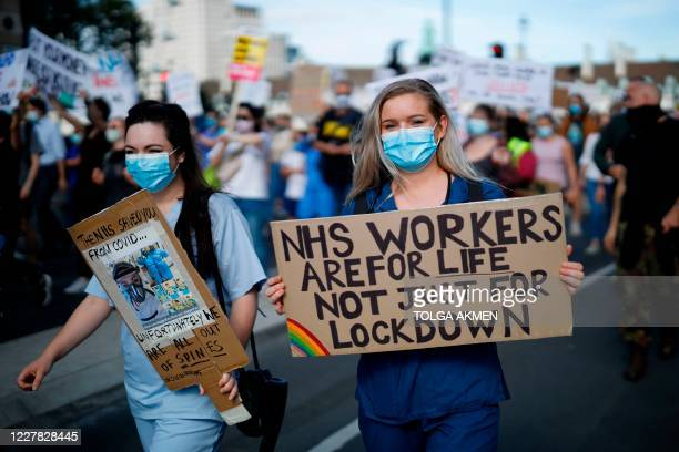 Staff hold banners as they march to Downing street in central London to demand a pay rise on July 29, 2020.