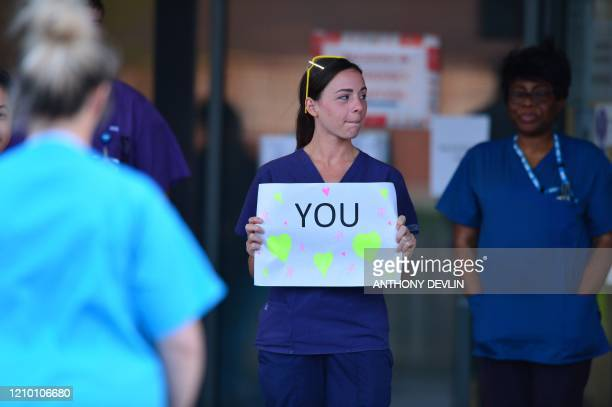 NHS staff hold up a sign to thank British veteran Captain Tom Moore who raised over 13 million GBP for the NHS as they take part in a national clap...