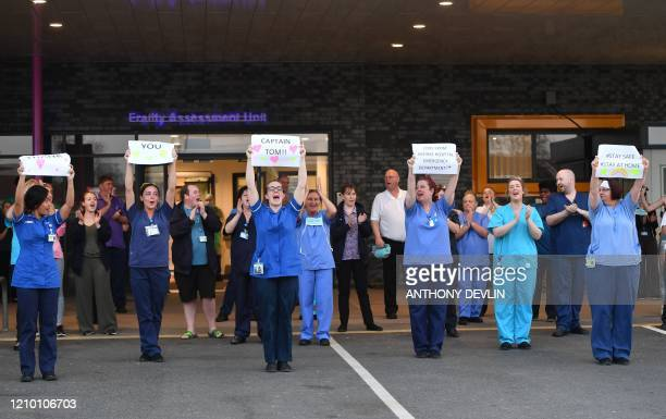 NHS staff hold up signs to thank British veteran Captain Tom Moore who raised over 13 million GBP for the NHS as they take part in a national clap...