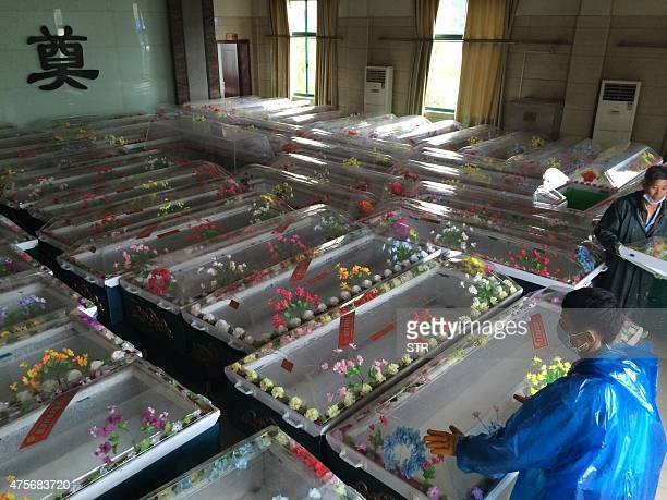 Staff in Jianli funeral parlor prepare ice coffins for victims who were travelling on the capsized passenger ship Dongfangzhixing or 'Eastern Star'...