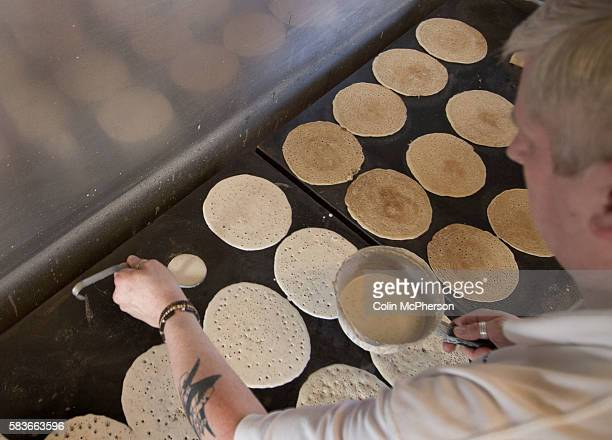 Staff in the tiny kitchen preparing and cooking oatcakes at the Hole in the Wall Oatcakes in StokeonTrent Staffordshire the last traditional oatcake...