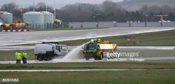 Staff inspect the runway at Bristol International Airport this morning after staff worked through the night to improve the drainage problem which has...