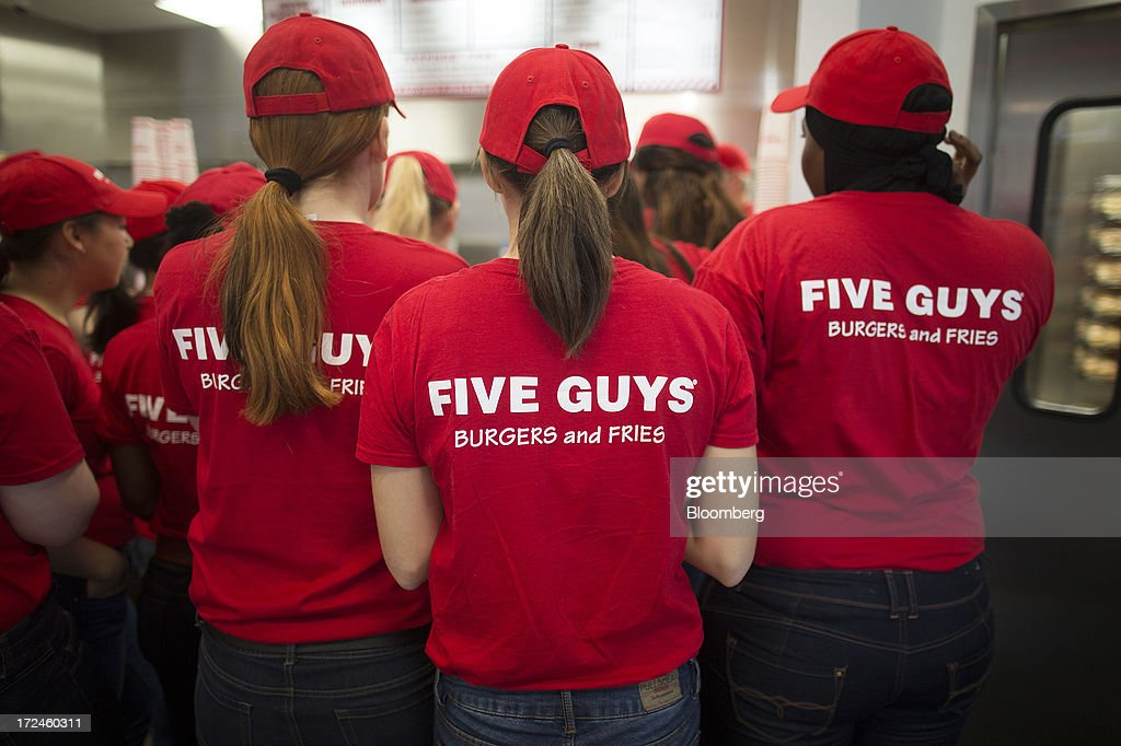 Staff listen during a training session inside the first U.K. outlet of U.S. burger restaurant chain Five Guys in London, U.K., on Tuesday, July 2, 2013. Five Guys, which is set to open its first U.K. store in Covent Garden on July 4, is a family outfit that started in Washington, D.C., in 1986, and has expanded to more than 1,000 locations in the U.S. and Canada. Photographer: Simon Dawson/Bloomberg via Getty Images