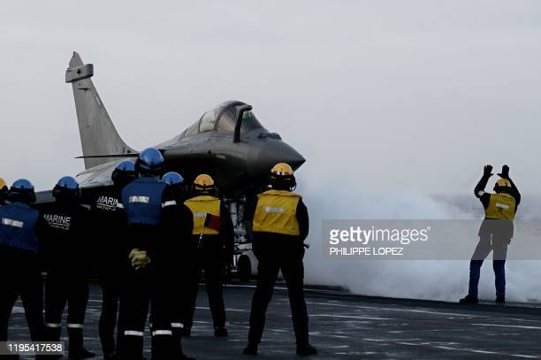 Staff look at a Rafale jet fighter about to take off the French aircraft carrier Charles de Gaulle at sea off the coast of the city of Hyeres on...