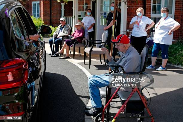 Staff look on as a visitor uses her phone to take a picture of her grandad during a drive-through visit at Gracewell, a residential care home in...
