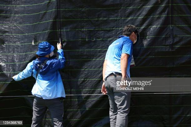 Staff look through as they hold a black sheet which is to cover the horse Jet Set of Switzerland's Robin Godel after the horse was injured in the...