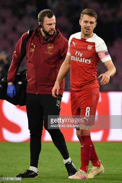 A staff medic escorts Arsenal's Welsh midfielder Aaron Ramsey as he leaves the pitch after he was injured during the UEFA Europa League quarterfinal...
