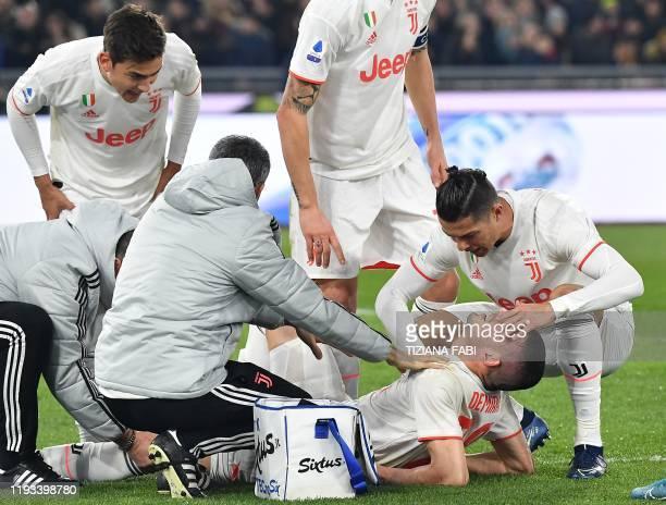 Staff medics Juventus' Argentine forward Paulo Dybala and Juventus' Portuguese forward Cristiano Ronaldo tend to Juventus' Turkish defender Merih...