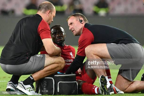 Staff medics tend to Liverpool's Guinean midfielder Naby Keita after he was injured during the UEFA Champions League group C football match between...