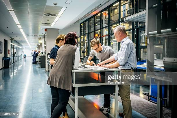 staff meeting close to a production line - engineer stock pictures, royalty-free photos & images
