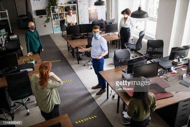 staff meeting in office with social distancing - witte boorden werker stockfoto's en -beelden