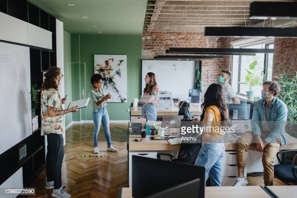staff meeting in office with social distancing - opening event stock pictures, royalty-free photos & images