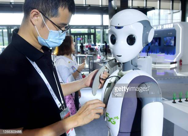 Staff member adjusts a robot developed by CloudMinds Technology Inc. During the 2020 World Artificial Intelligence Conference at Shanghai EXPO Centre...
