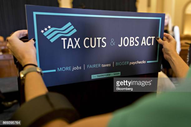 A staff member adjusts a sign on a podium before a news conference on tax reform on Capitol Hill in Washington DC US on Thursday Nov 2 2017 House...