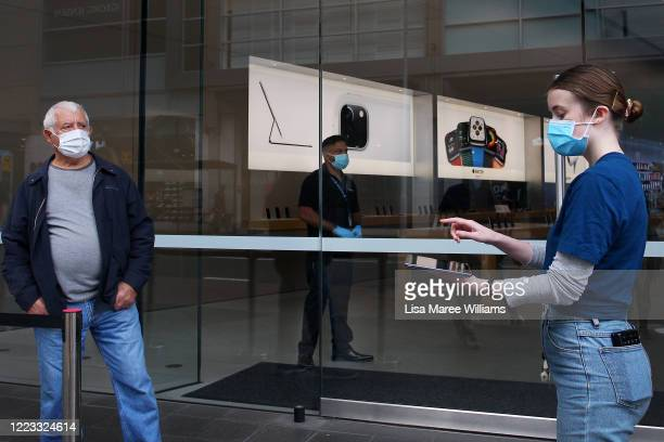 Staff member assists a customer prior to entering the Bondi Junction Apple Store on May 07, 2020 in Sydney, Australia. Apple stores across Australia...